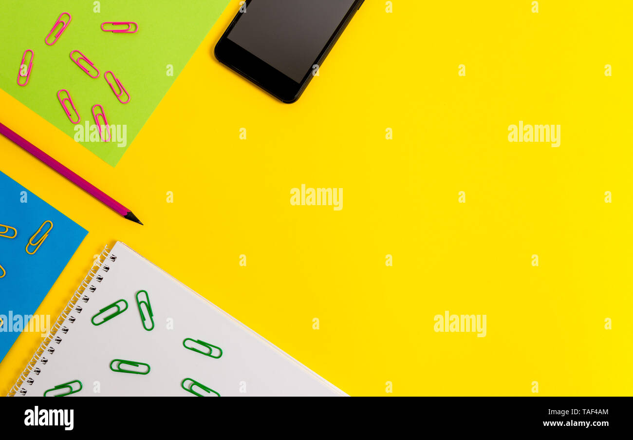 Sheets message pencil clips binders smartphone plain colored background - Stock Image