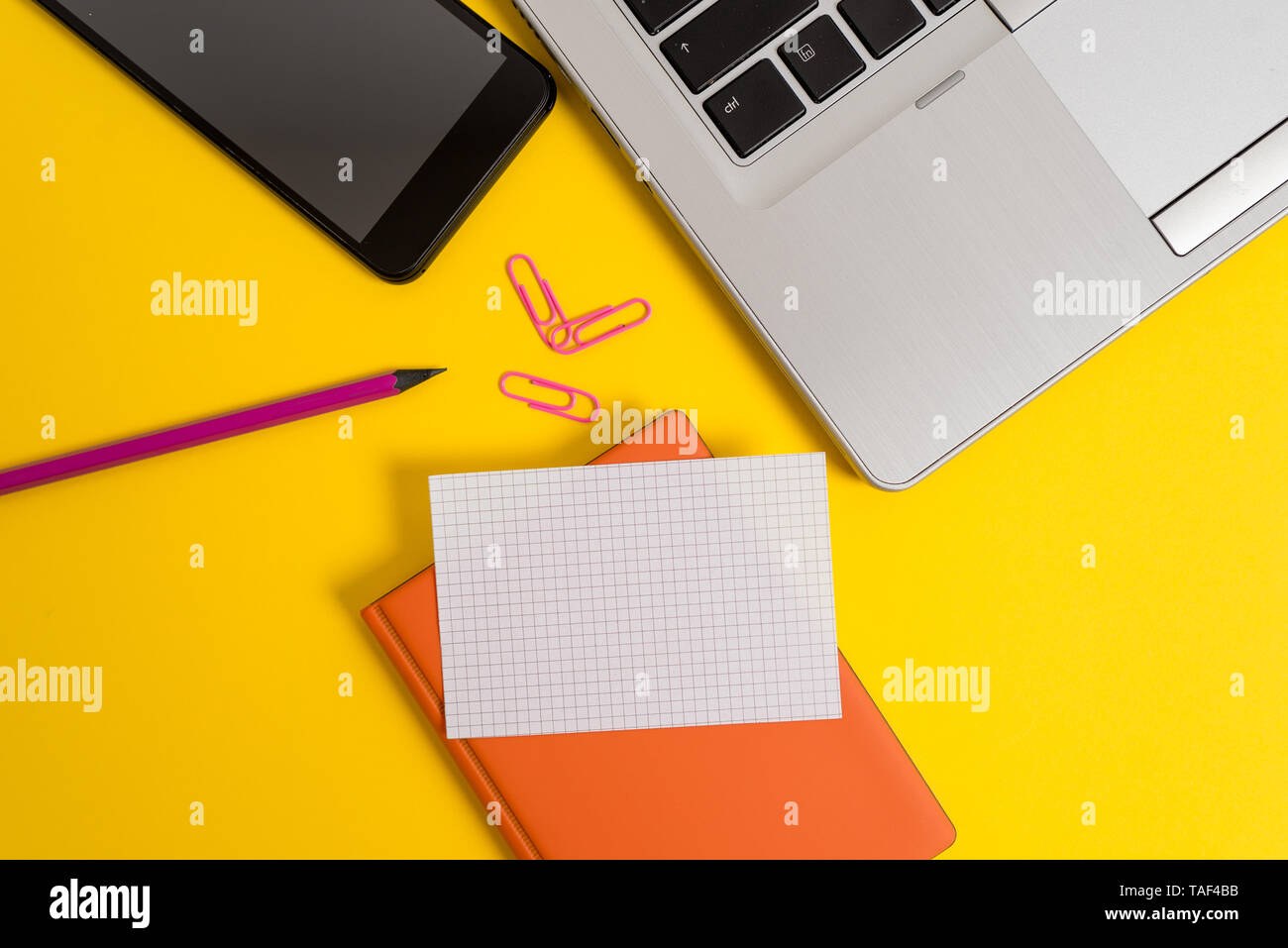 Laptop smartphone clips pencil paper sheet notebook colored background - Stock Image