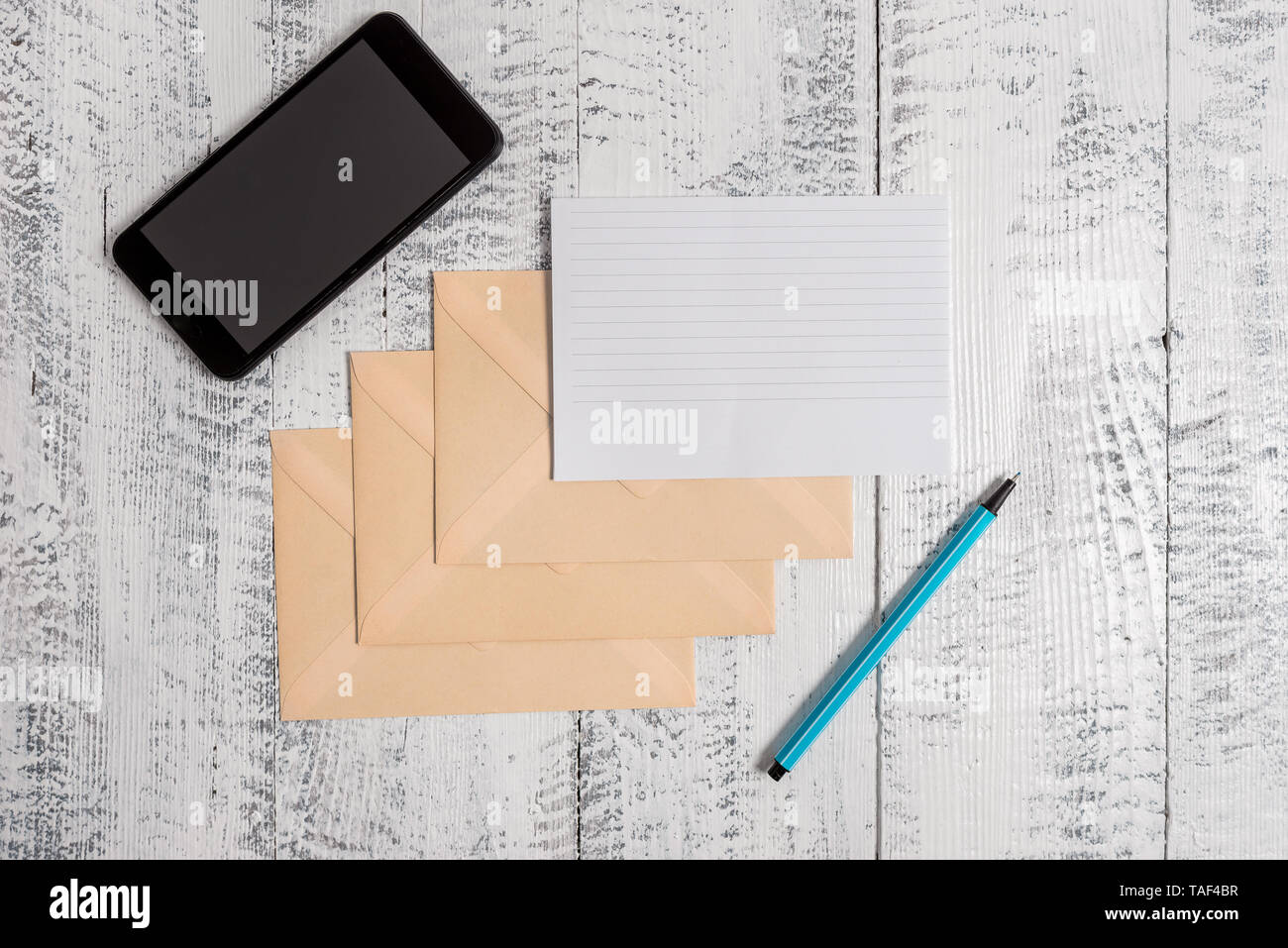 Three envelopes marker ruled paper smartphone sheet wooden background - Stock Image
