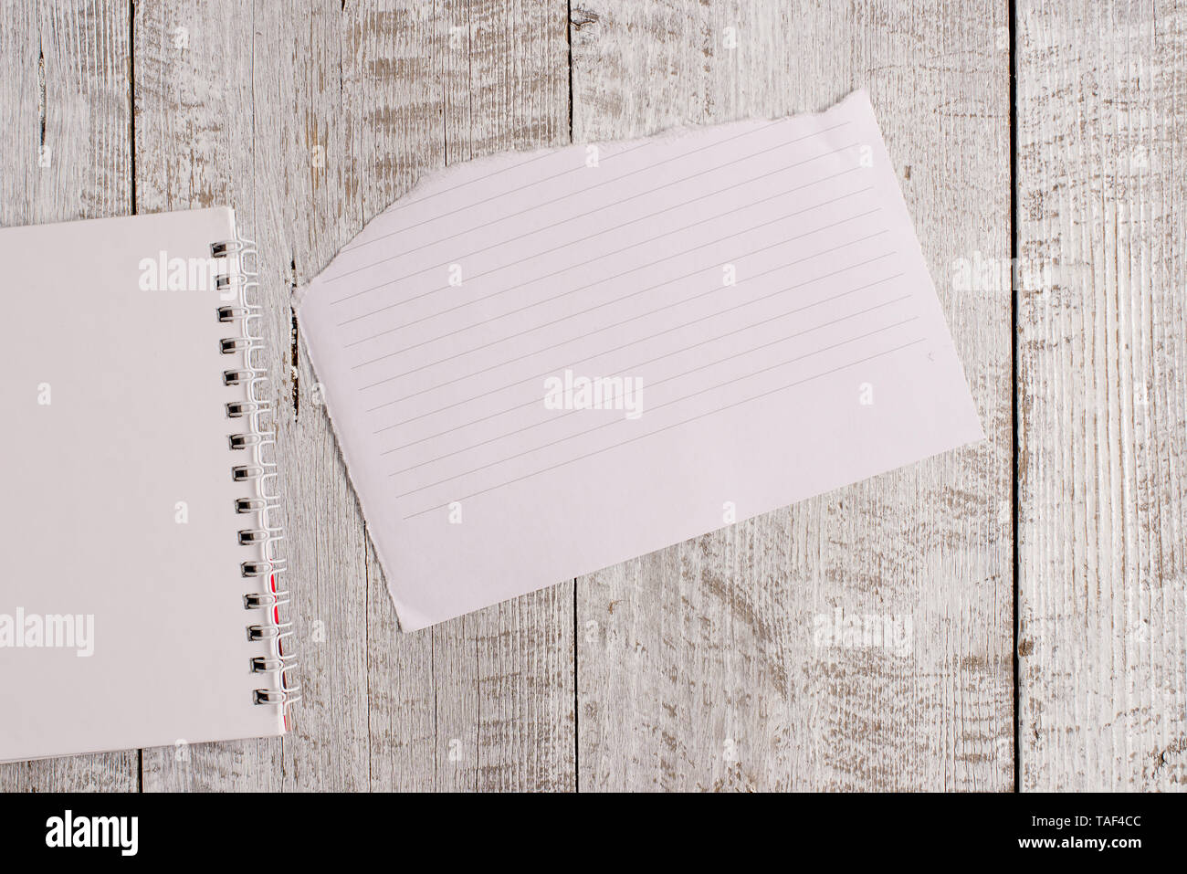 Torn paper and notebook sheet placed on top of a classic wooden table. - Stock Image