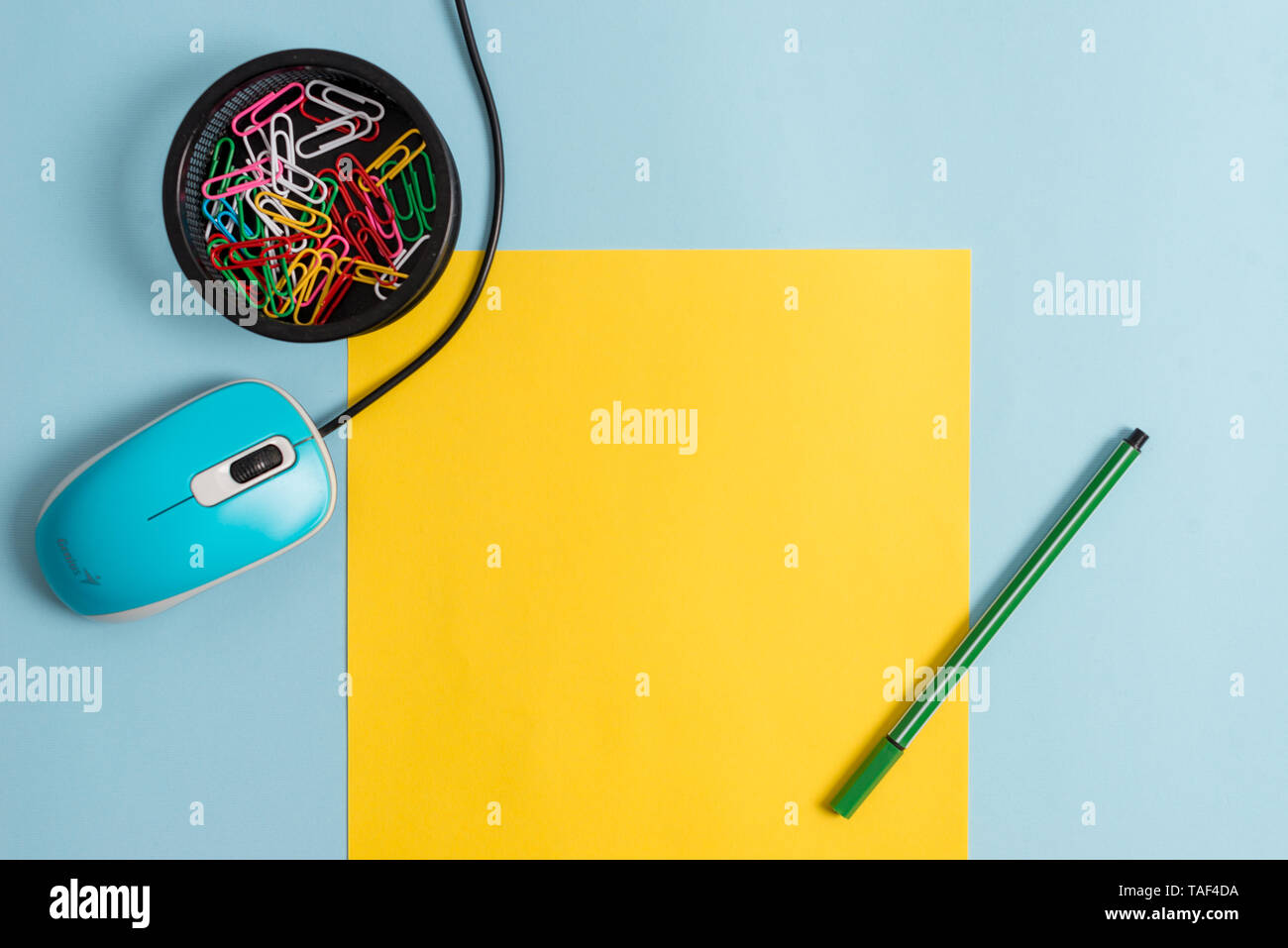 Cardboard and writing equipment with modern gadget above pastel backdrop - Stock Image