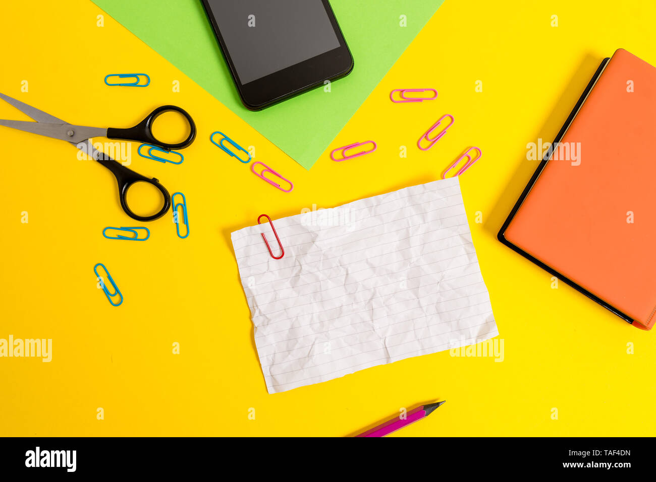 Paper sheets pencil clips smartphone scissors notebook colored background - Stock Image