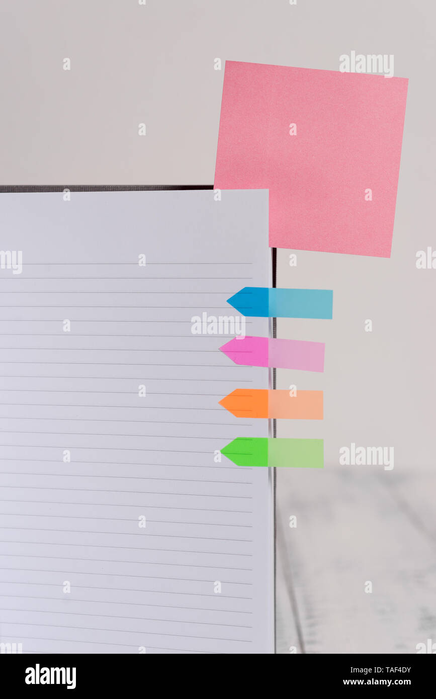 Hard cover note book sticky note arrow banners inserted clear background - Stock Image