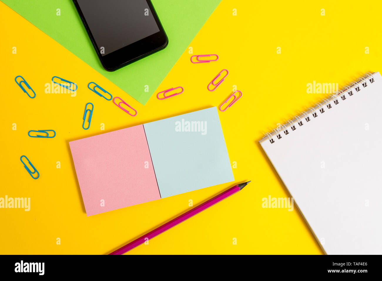 Square blank sticky notepads pencil clips smartphone sheet color background - Stock Image