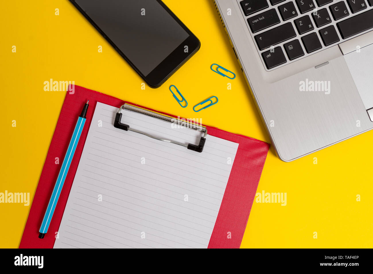 Open laptop clipboard sheet smartphone marker clips colored background - Stock Image