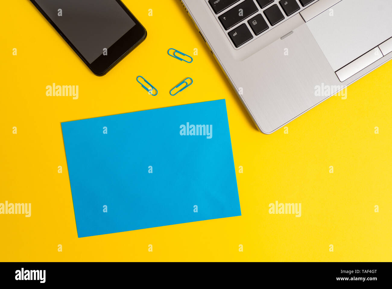 Trendy open laptop smartphone small paper sheet clips colored background - Stock Image