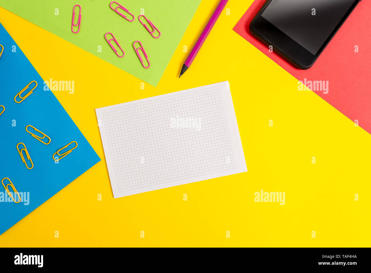 Paper sheets pencil clips smartphone squared notebook colored background - Stock Image
