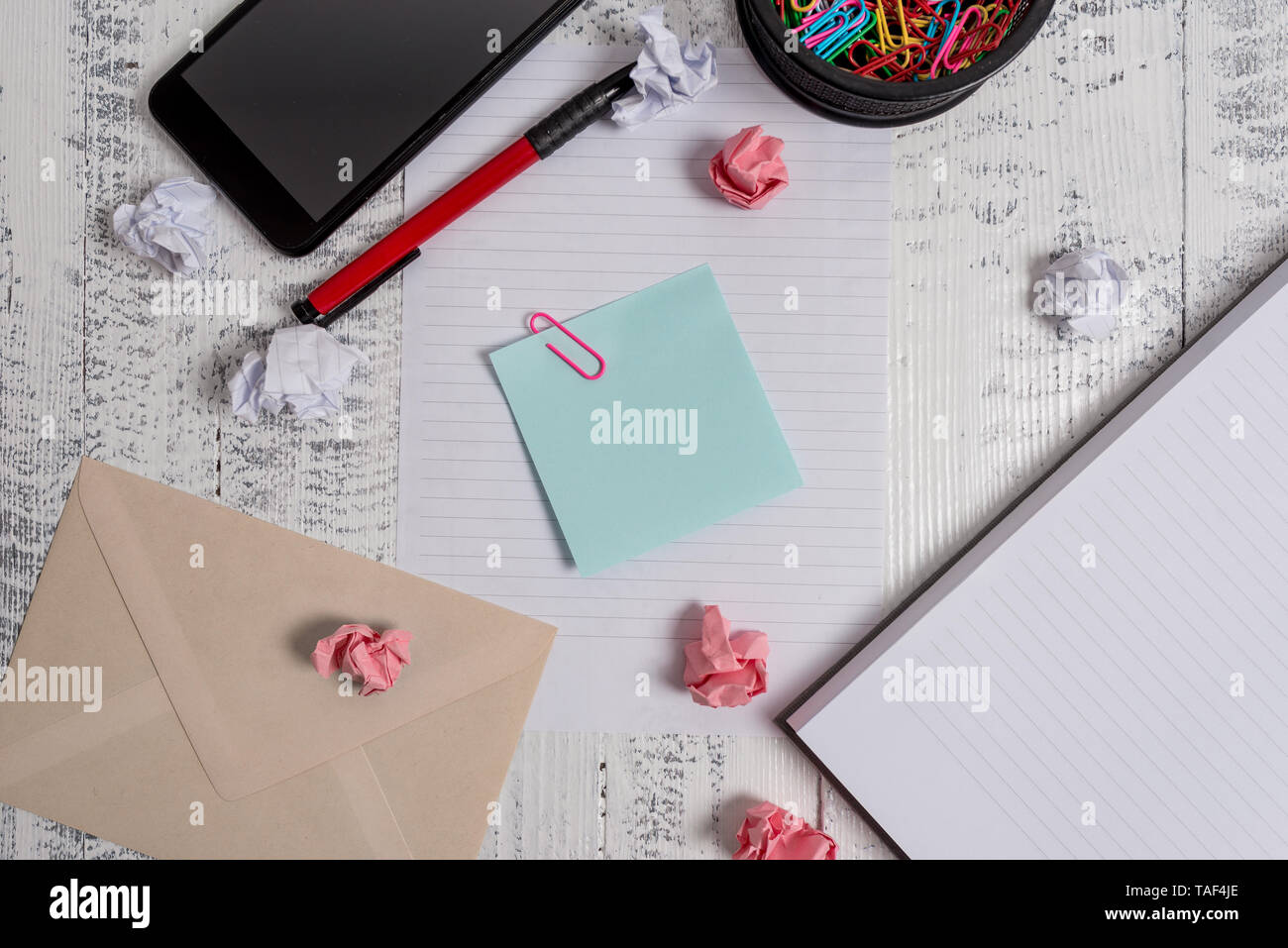 Smartphone sheet clips pen notebook paper balls envelope note wooden back - Stock Image
