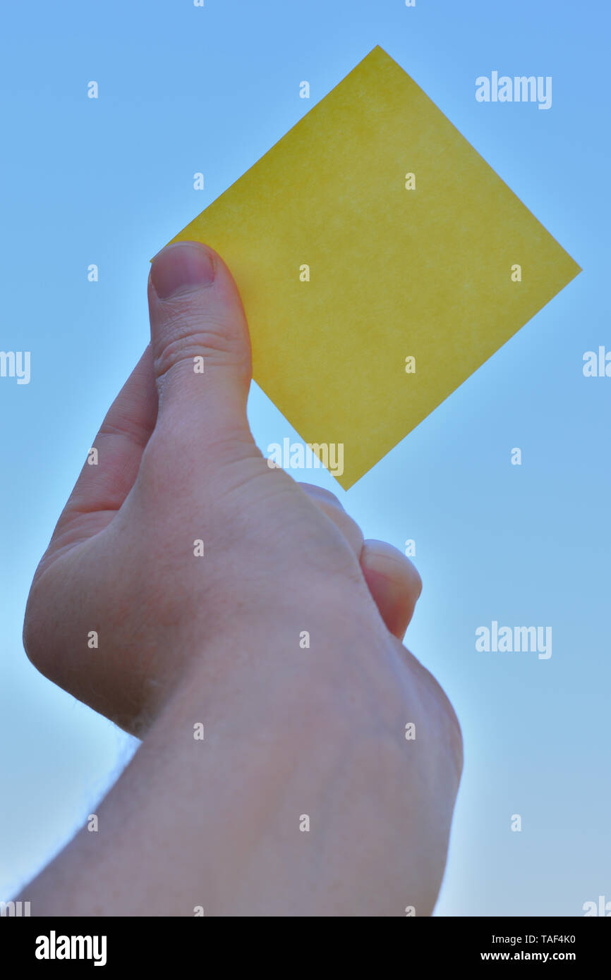 Piece of square paper use to give notation hold by one hand raising up - Stock Image