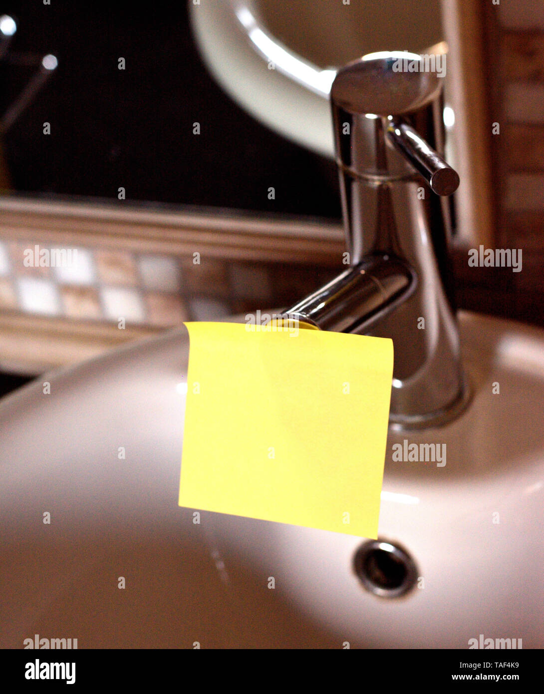 Piece of square paper use to give notation stick to water tap in bathroom - Stock Image