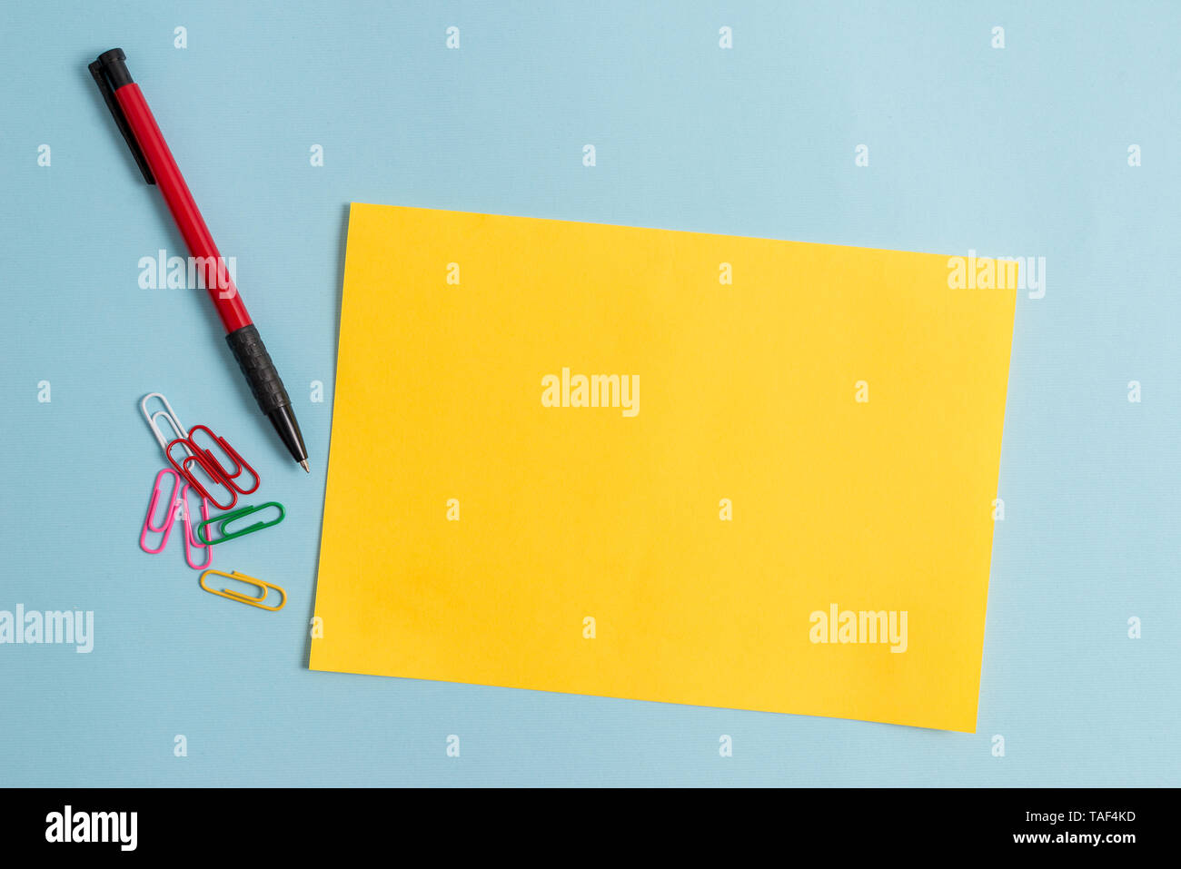 Plain cardboard and writing equipment placed above pastel colour backdrop - Stock Image