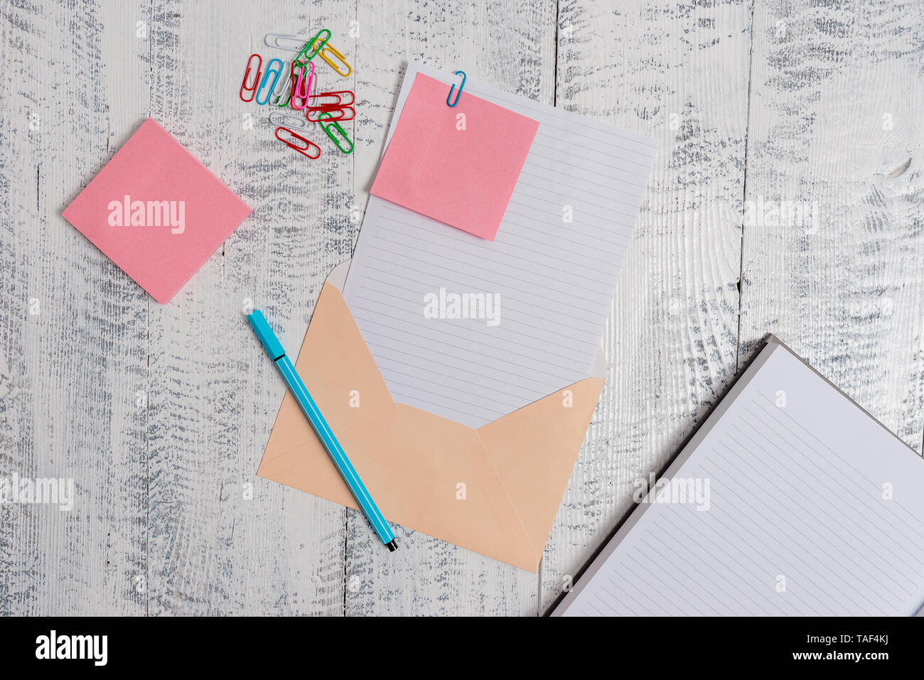 Envelope sheet paper sticky notes ballpoint notepad clips wooden background - Stock Image