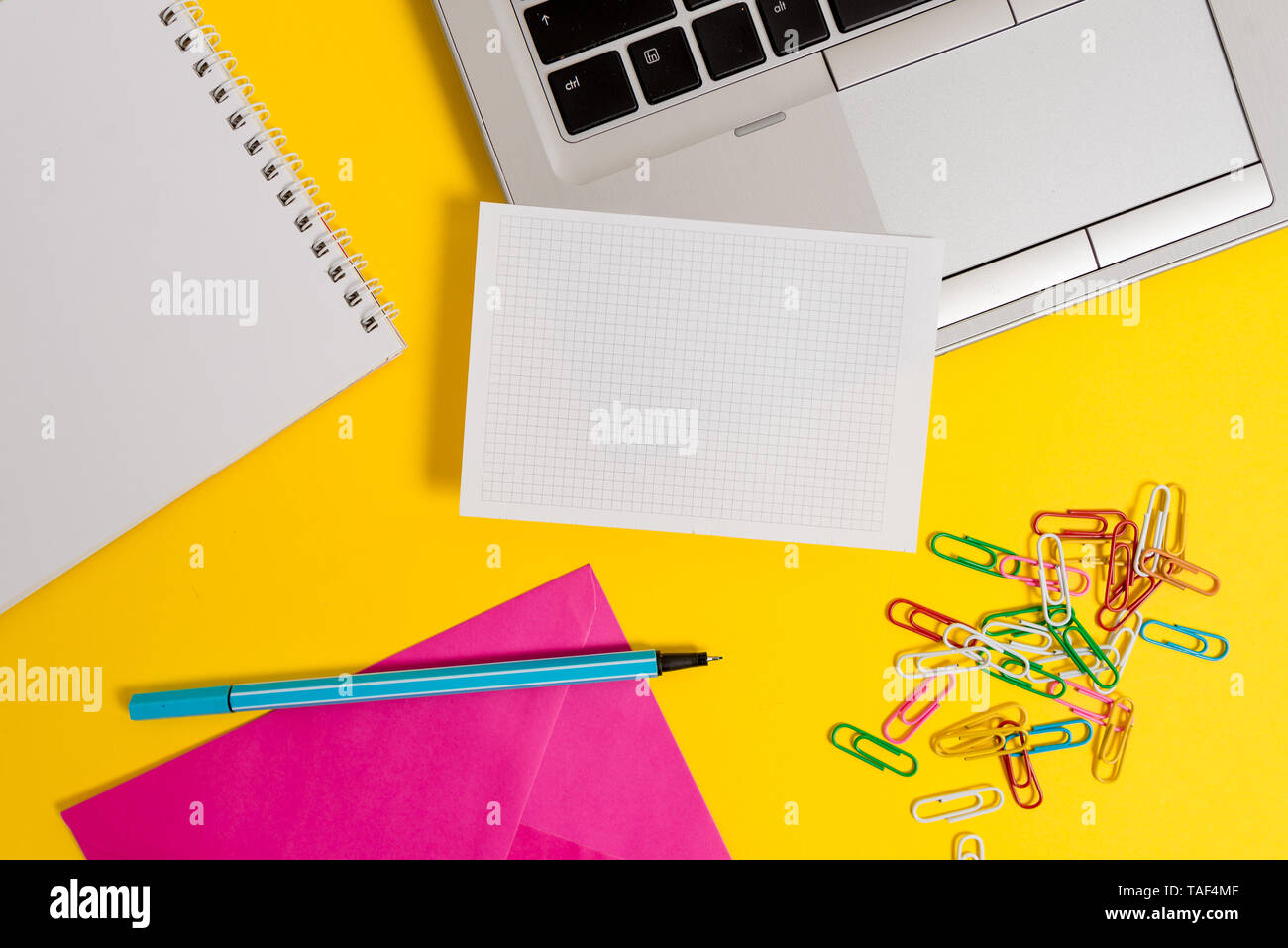 Laptop marker squared sheet spiral notebook clips envelope color background - Stock Image