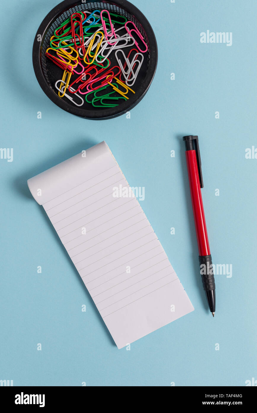 Notebook and writing equipment with computer mouse above pastel backdrop - Stock Image
