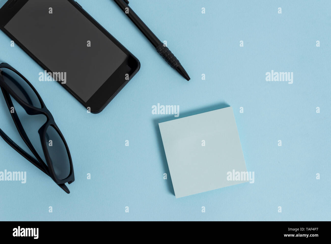 Eyeglasses colored sticky note smartphone cell pen cool pastel background - Stock Image