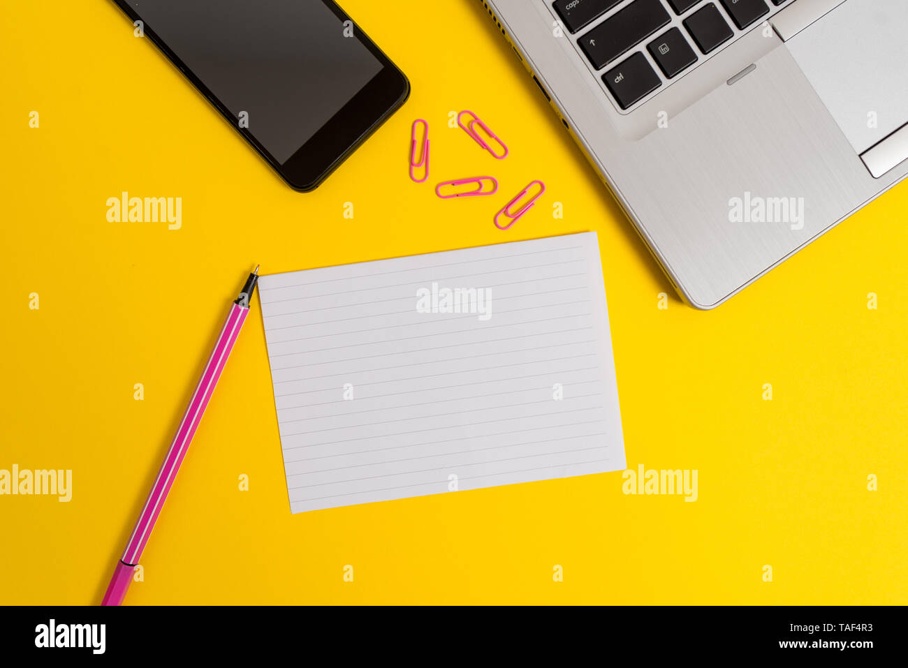 Trendy open laptop smartphone marker paper sheet clips colored background - Stock Image