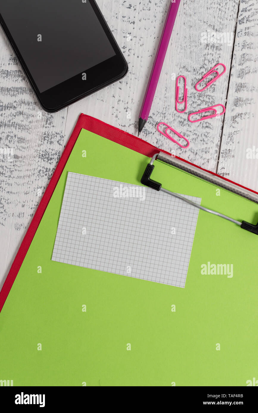 Clipboard sheet pencil smartphone squared note clips wooden background Stock Photo