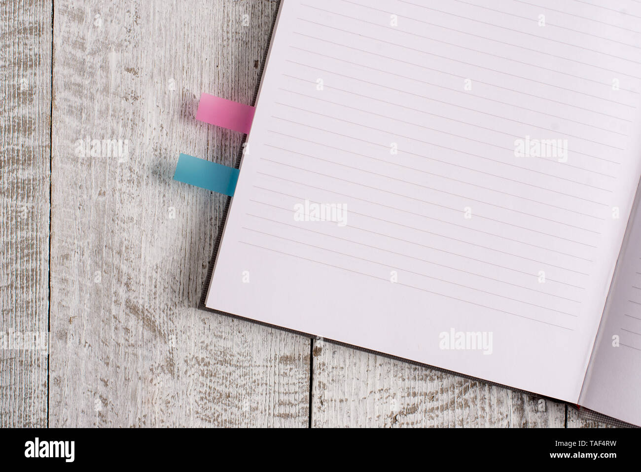 Thick pages notebook stationary placed above classic look wooden backdrop - Stock Image