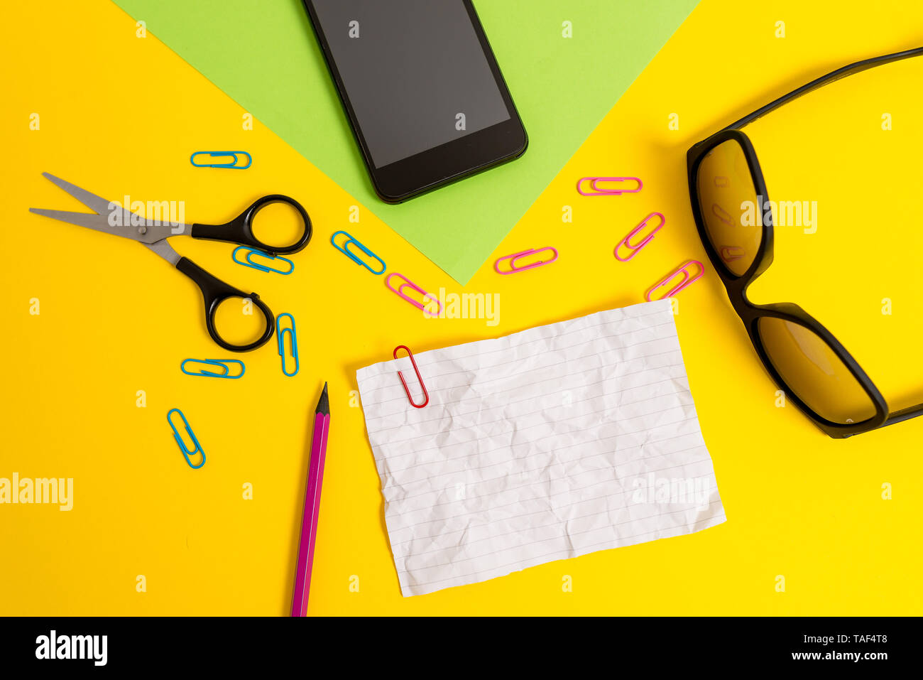 Paper sheets pencil clips smartphone scissors eyeglasses colored background Stock Photo