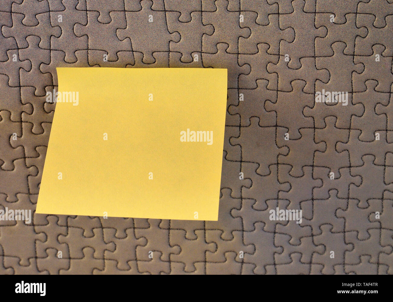 Piece of square note paper use for give notation stick to puzzle background Stock Photo