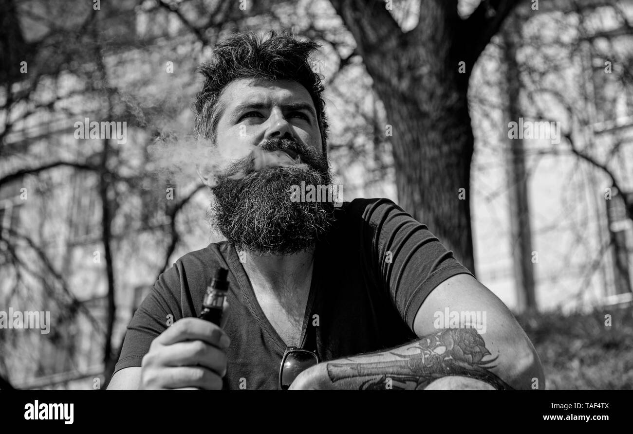 Hipster with tousled hair and gray on relaxed dreamy face with white smoke flying out of mouth. Vaping and habits concept. Man with beard and mustache smoking, urban background. - Stock Image