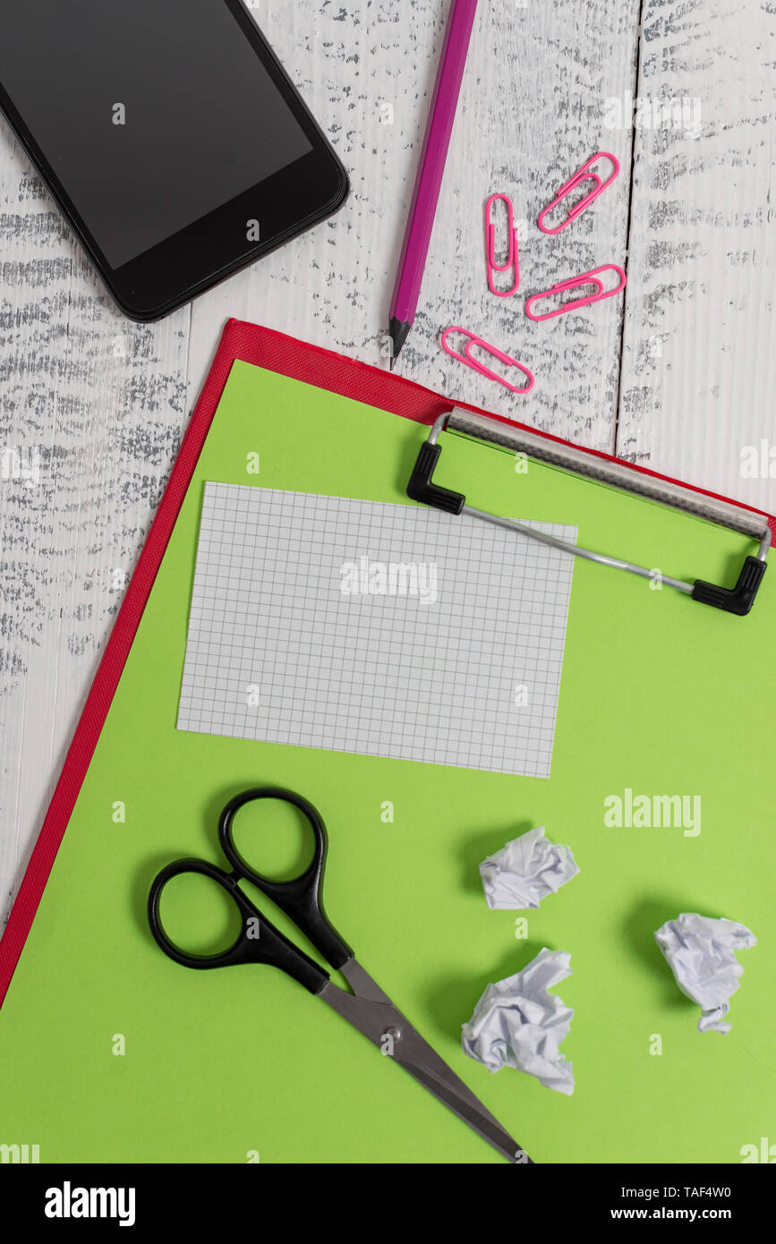 Clipboard paper sheet pencil smartphone scissors note clips balls wooden - Stock Image