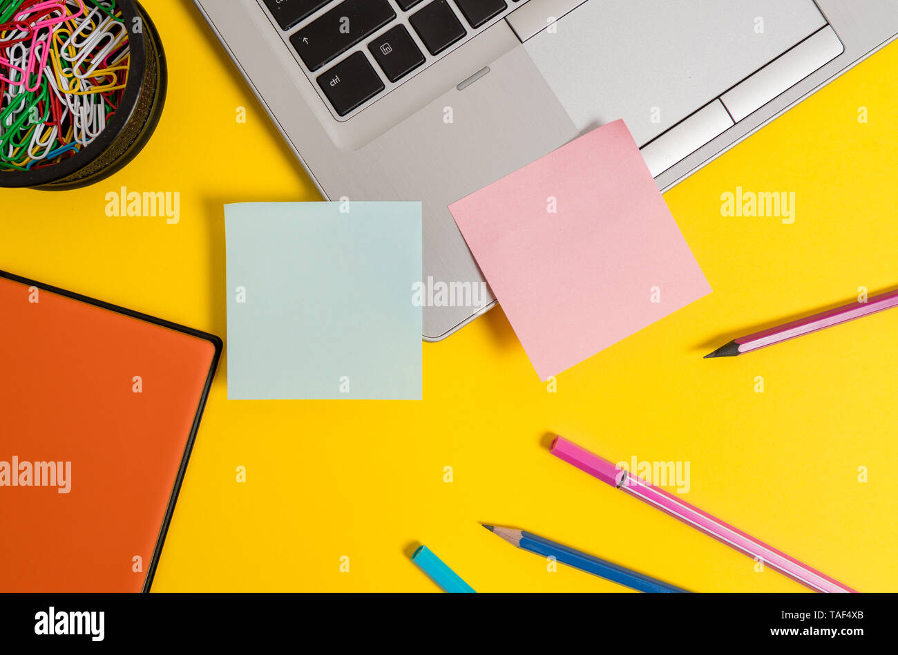 Laptop notes clips container notepad pencils markers colored background Stock Photo