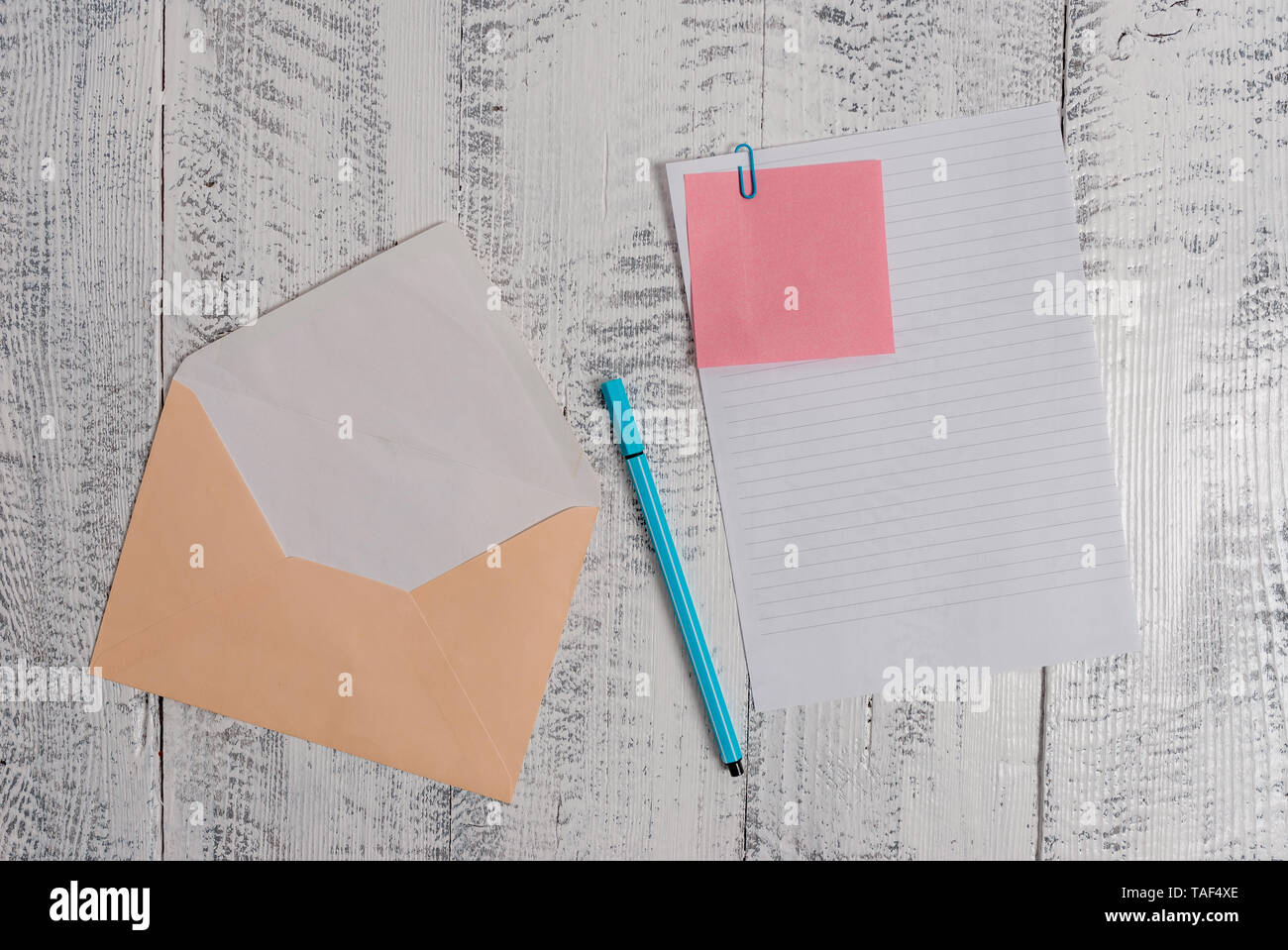 Envelope blank sheet letter paper sticky note ballpoint wooden background - Stock Image