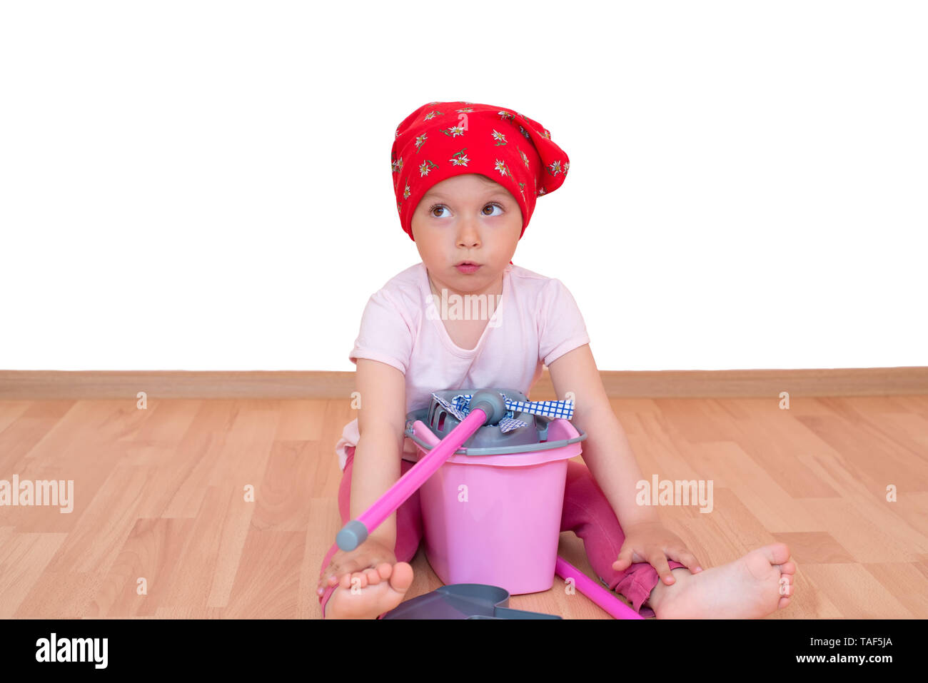 Barefoot little girl with mop and bucket sitting on the floor isolated - Stock Image