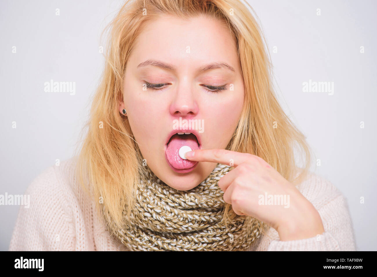 Home treatment concept. Girl take medicine to break fever. Cold flu and sore throat. Bitter pill to swallow. Headache and Take tablet relieve fever. fever remedies. Woman sick person hold tablet. - Stock Image