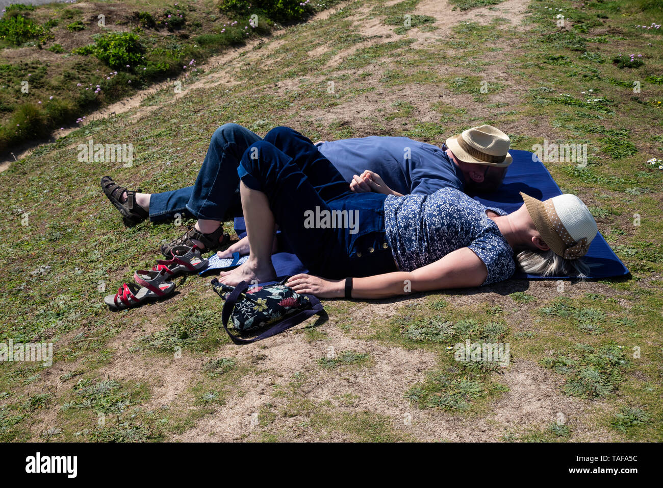 A middle aged couple with hats over their faces sunbathing and dozing on a grassy mound - Stock Image