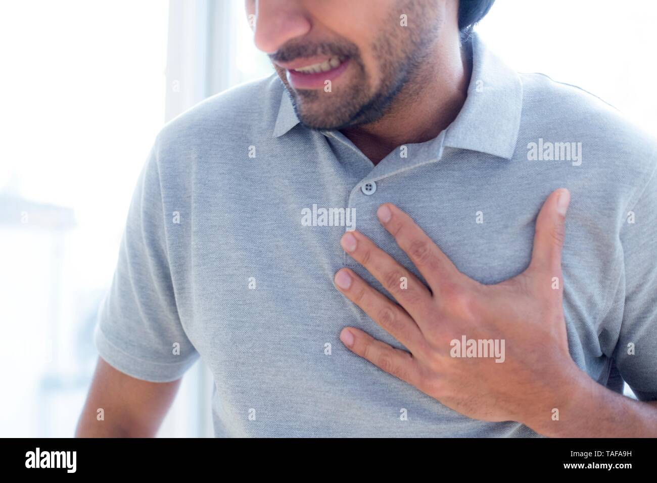 Man touching his chest in pain - Stock Image
