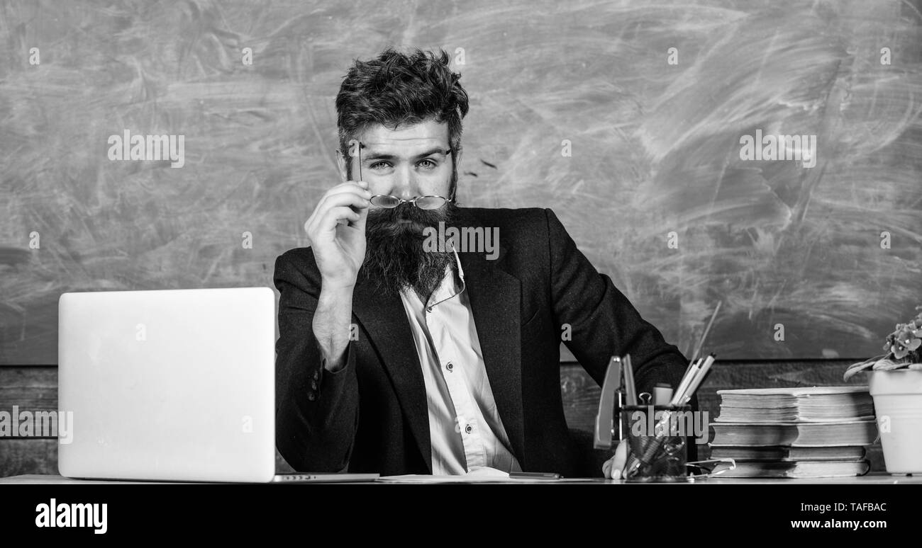 Teacher formal wear sit table classroom chalkboard background. Teacher concentrated bearded mature schoolmaster listening with attention. Teacher listening answer or report. Pay attention to details. - Stock Image