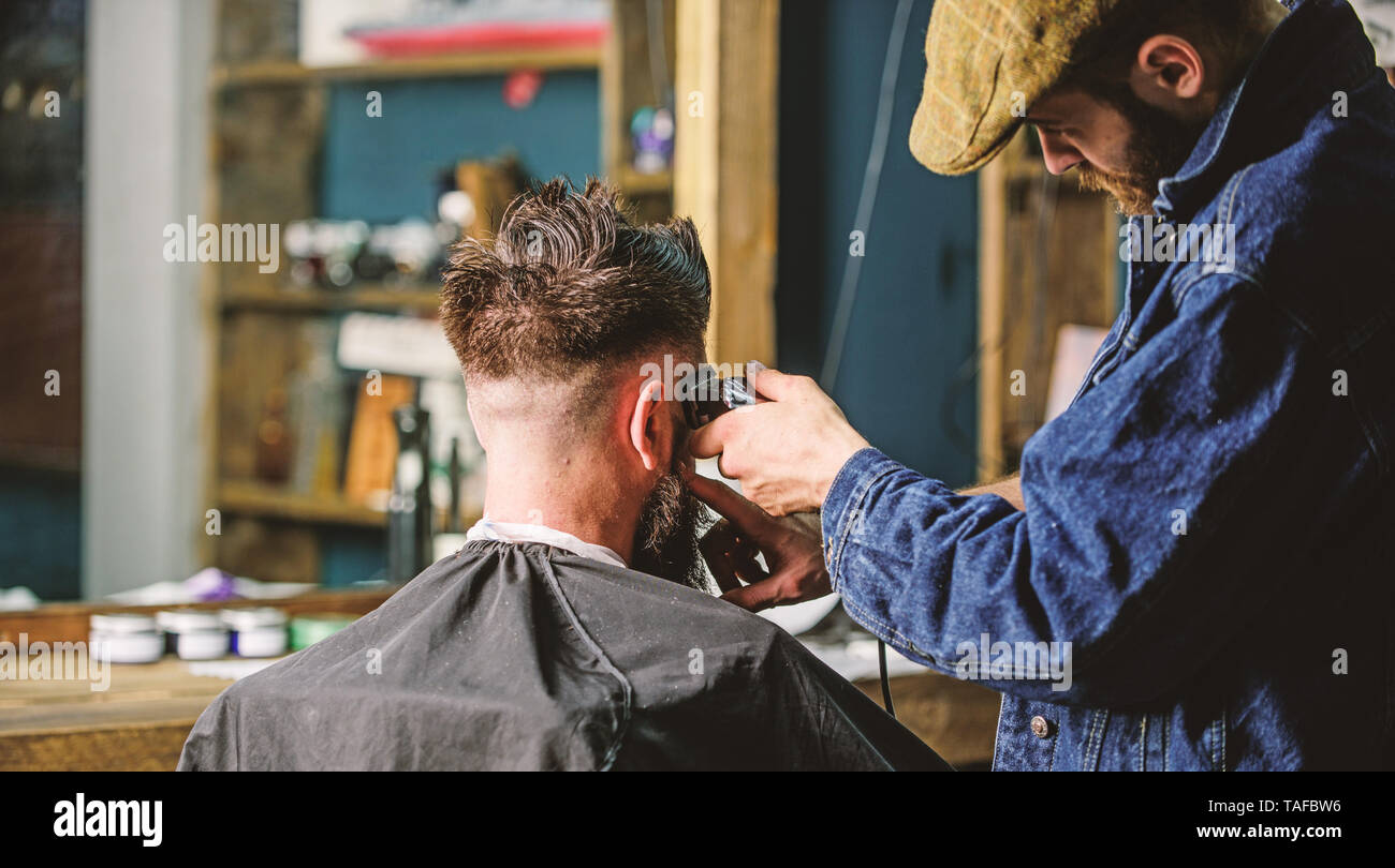 Barber With Clipper Trimming Hair Of Client Rear View Working Process Concept Barber With Hair Clipper Works On Short Haircut On Teple Barbershop Background Hipster Client Getting Short Haircut Stock Photo