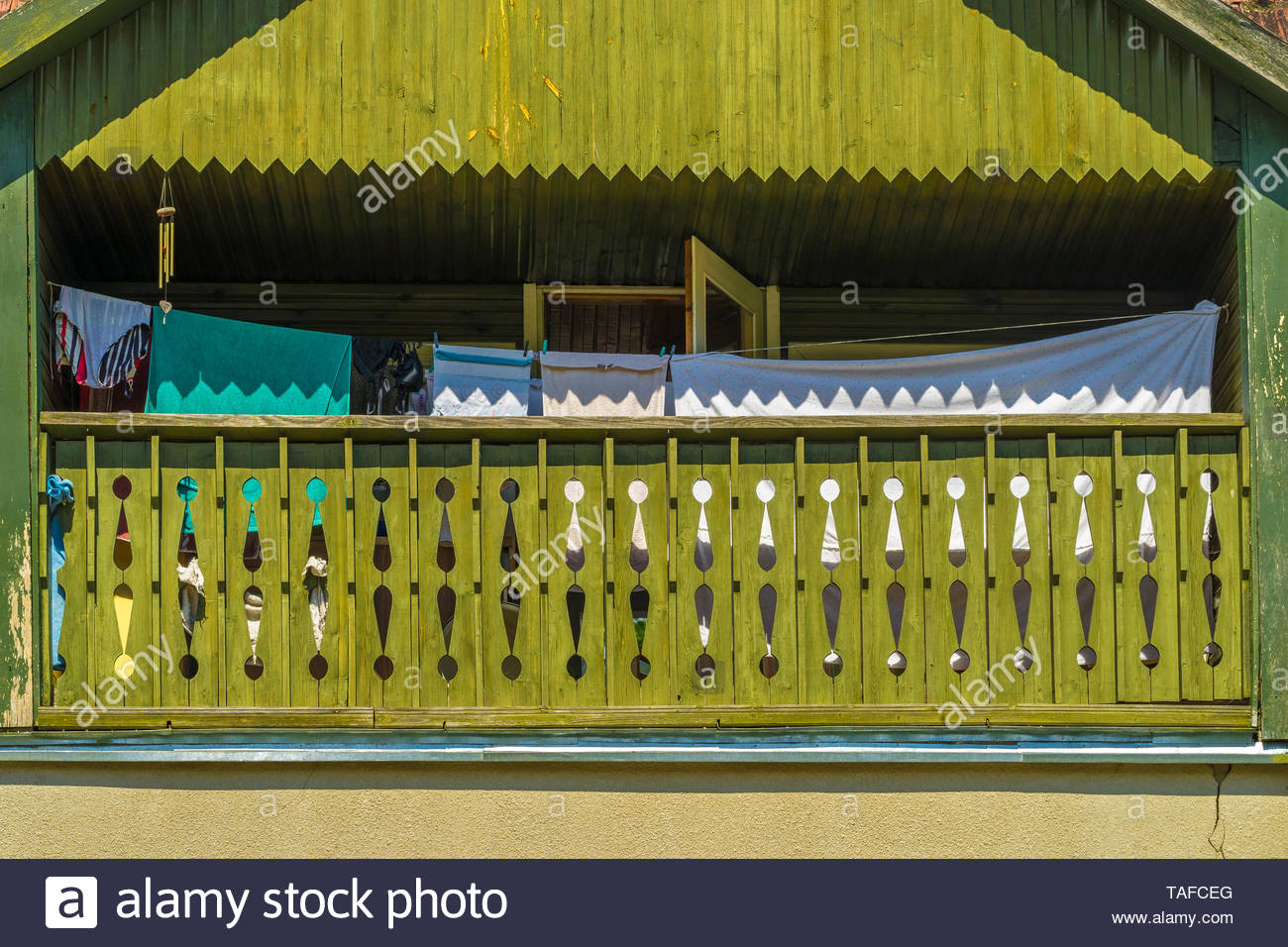 Green painted wooden balcony of the house with laundry on a sunny hot summer day. The front of the balcony is decorated with geometric patterns wood c - Stock Image