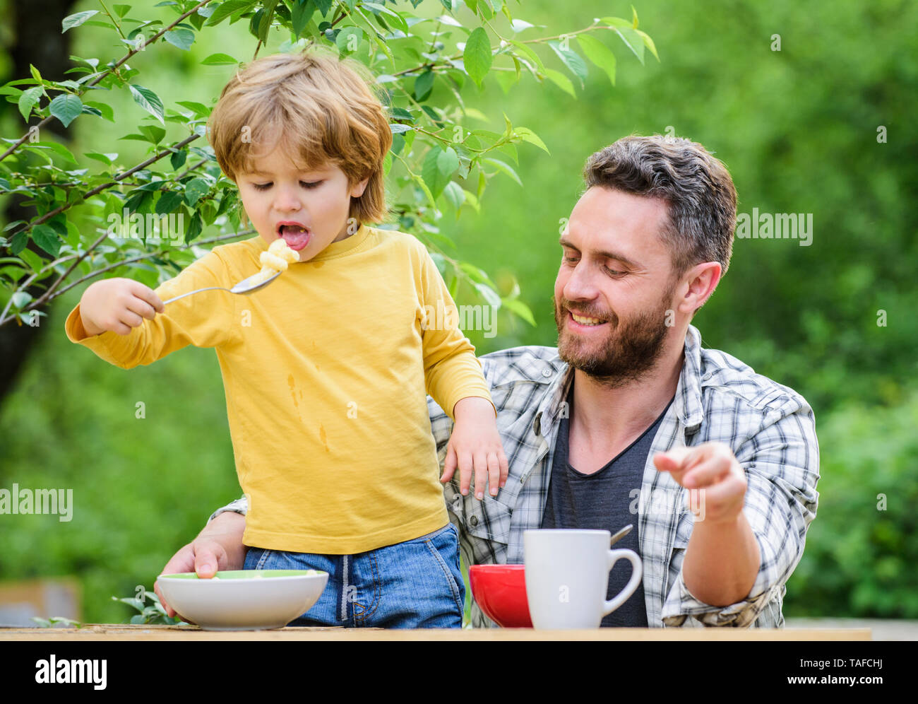 Father son eat food and have fun. Food habits. Little boy with dad eating food nature background. Summer breakfast. Healthy food concept. Feeding baby. Menu for children. Family enjoy homemade meal. - Stock Image