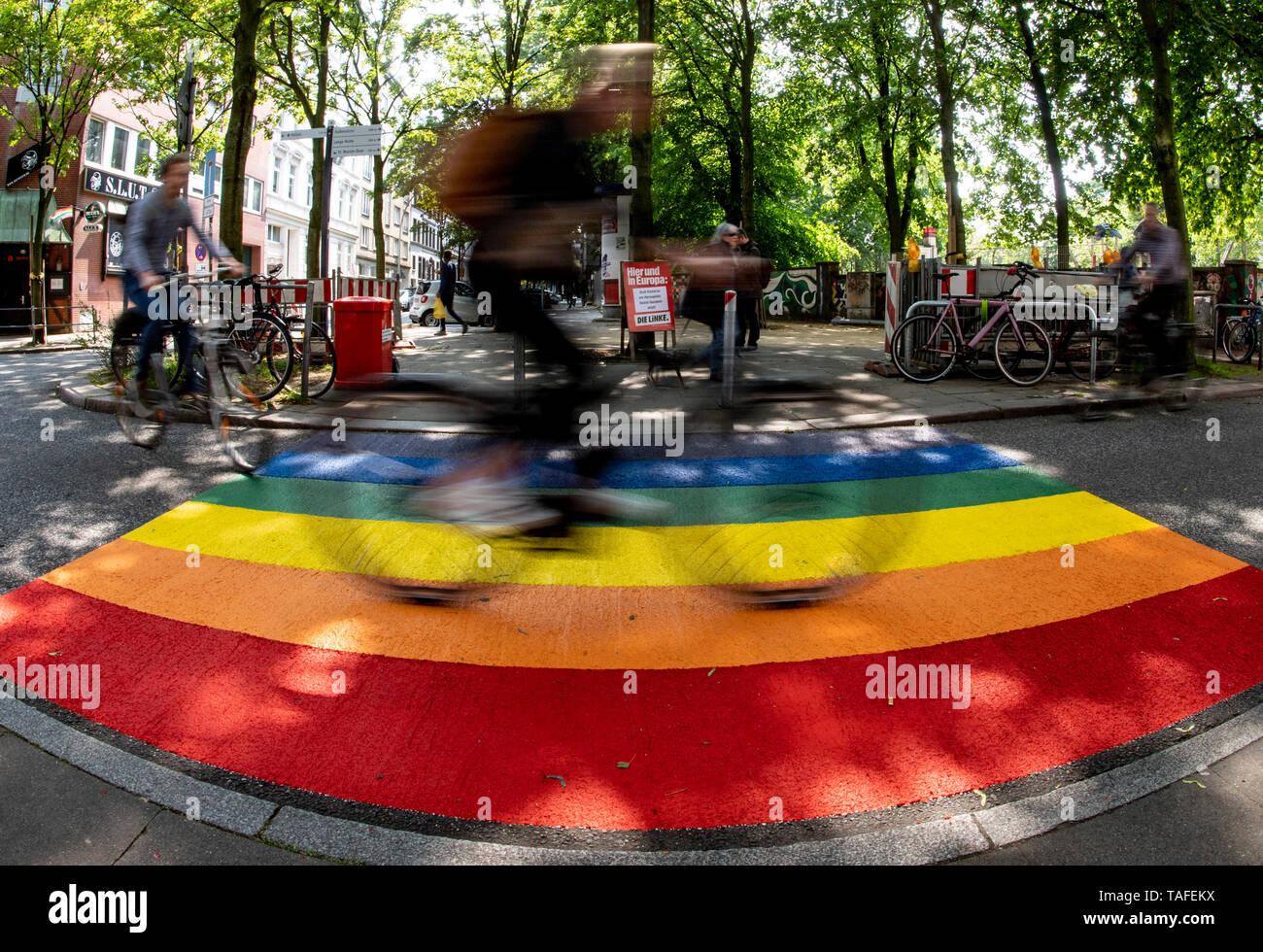 24 May 2019, Hamburg: A cyclist passes a new rainbow marker