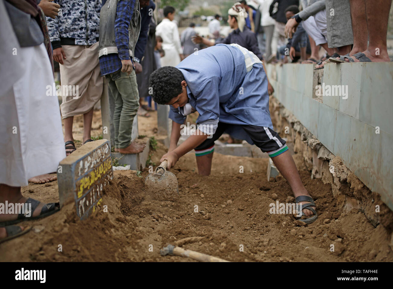 Sanaa, Yemen. 24th May, 2019. Yemeni people bury the bodies of the victims who were killed in an air strike allegedly carried out by the Saudi-led coalition. Credit: Hani Al-Ansi/dpa/Alamy Live News - Stock Image