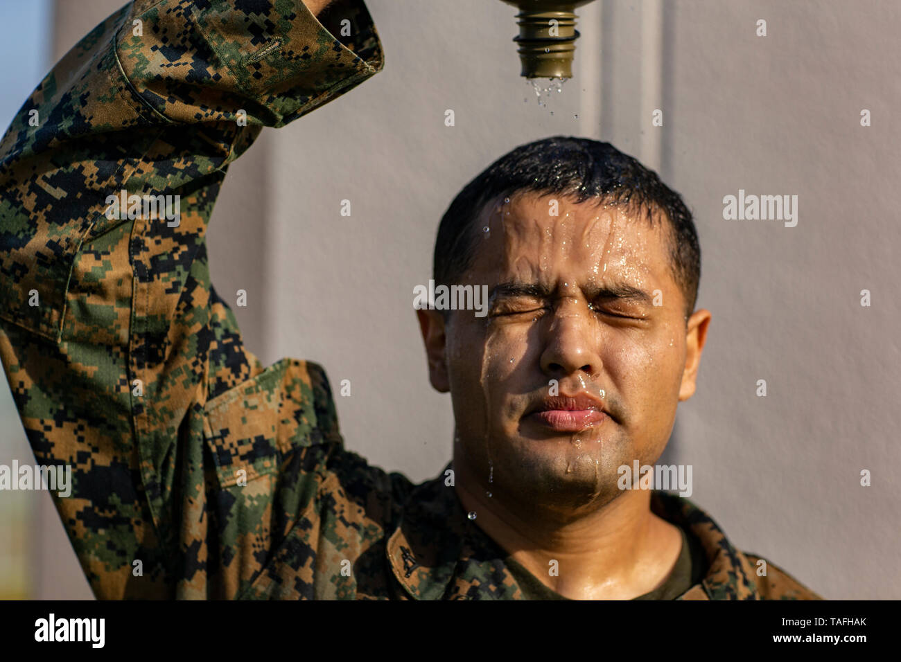 Iwakuni, Japan. 23rd May, 2019. U.S. Marine Corps Lance Cpl. Cesar Ramirez pours a canteen of water on his head to cool off after a conditioning hike on a hot day at Marine Corps Air Station May 23, 2019 in Iwakuni, Japan. Credit: Planetpix/Alamy Live News Stock Photo