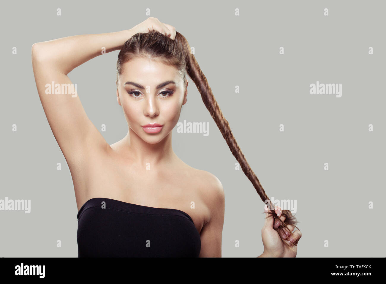 beautiful woman holding straight shiny strong hair. Gray background Stock Photo
