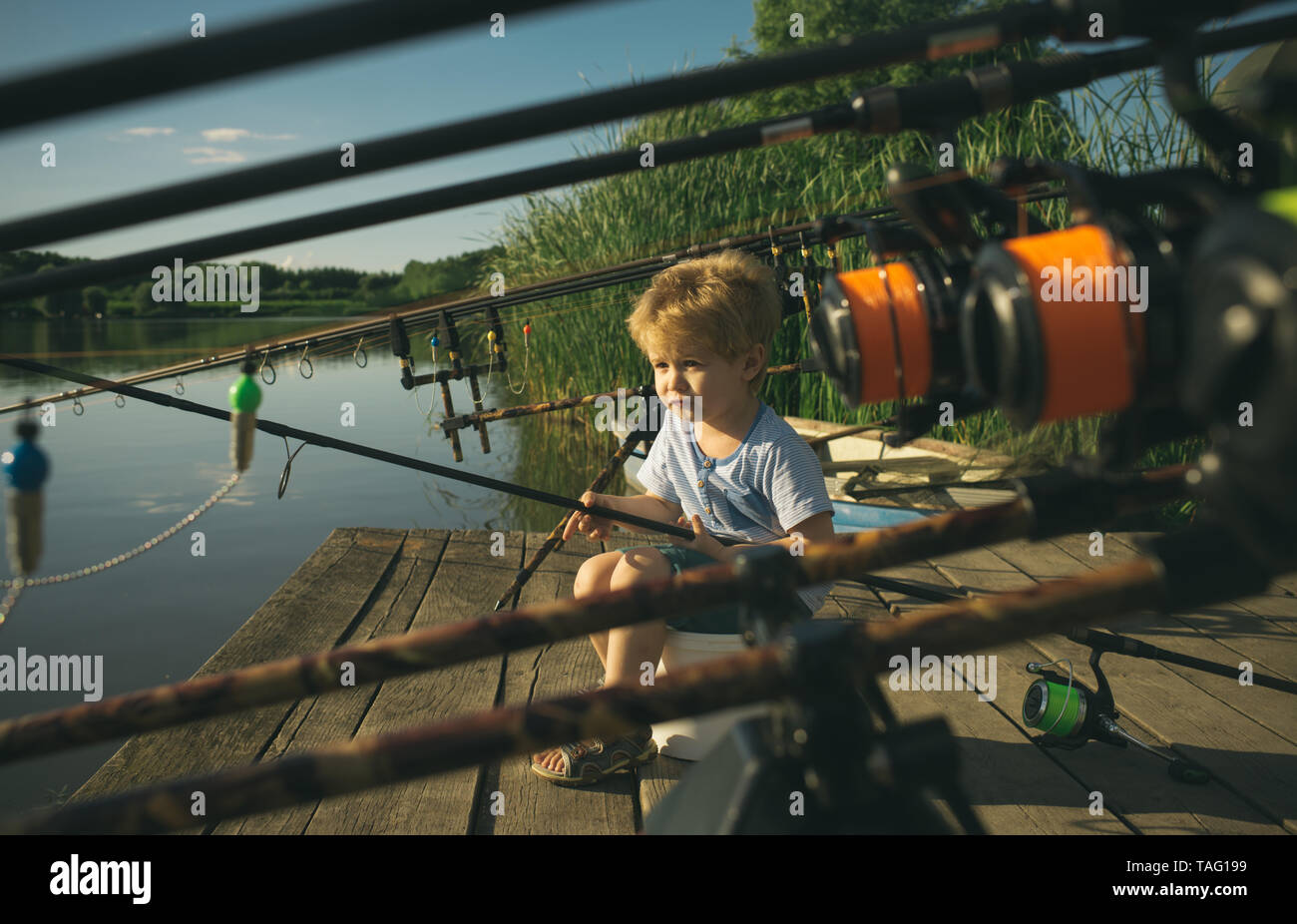 679e0b8f1efe7 Little baby boy fishing on bank of river with fishing rod in hands ...