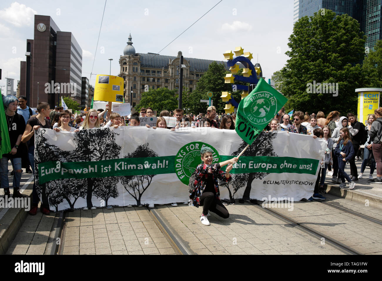 The people at the banner at the front of the march pose for a picture. The large Euro sign can be seen in the background. Around 4,500 young people marched through Frankfurt to the European Central Bank, to protest against the climate change and for the introduction of measurements against it. The protest took place as part of an Europe wide climate strike, two days ahead of the 2019 European elections. (Photo by Michael Debets/Pacific Press - Stock Image