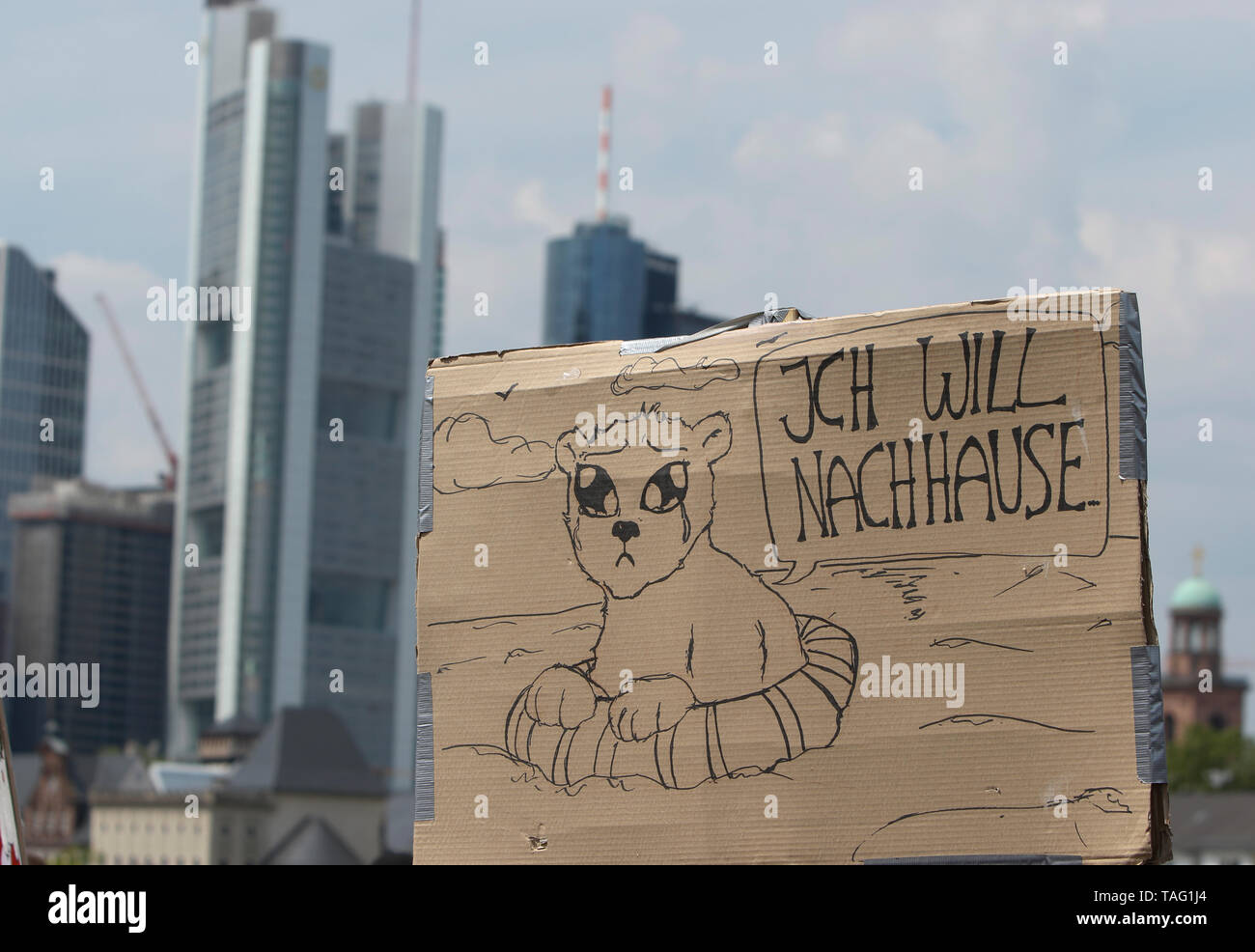 A protester carries a sign that reads 'I want to go home', with the drying of a Polar Bear in a lifebuoy. The Frankfurt skyline can be seen in the background. Around 4,500 young people marched through Frankfurt to the European Central Bank, to protest against the climate change and for the introduction of measurements against it. The protest took place as part of an Europe wide climate strike, two days ahead of the 2019 European elections. (Photo by Michael Debets/Pacific Press - Stock Image