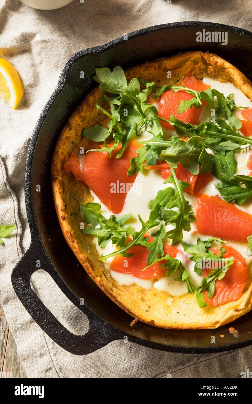 Homemade Savory Dutch BAby Pancake with Salmon and Arugula - Stock Image