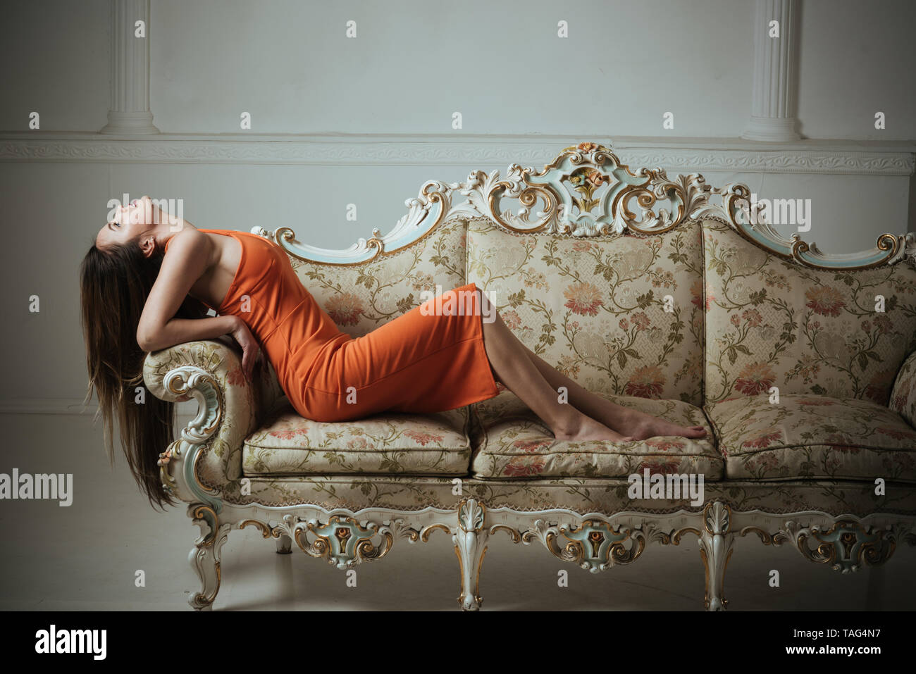 Woman with long healthy hair relax on sofa. Your hair is our best advert. Stock Photo