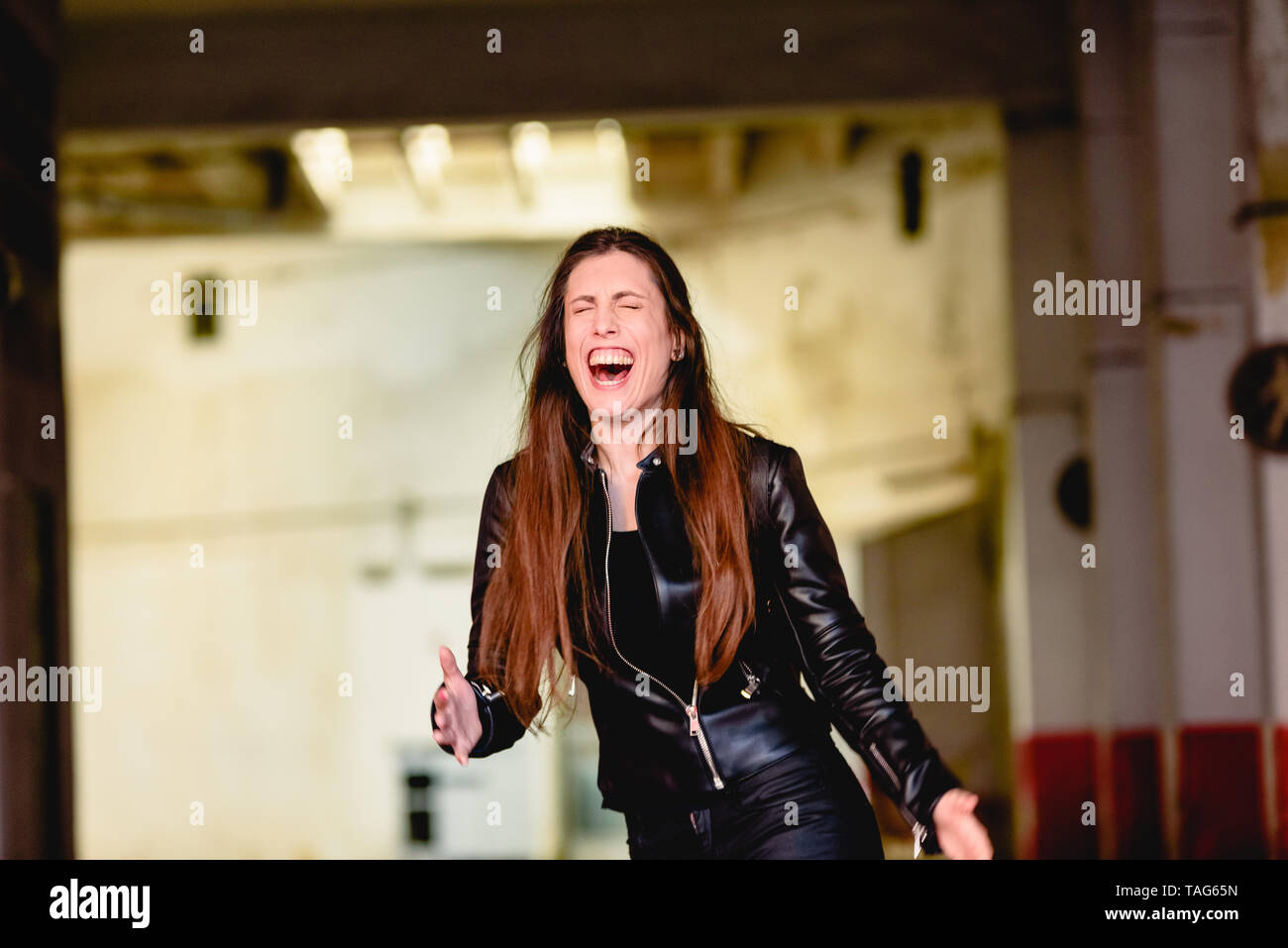 Young woman laughing loudly. - Stock Image