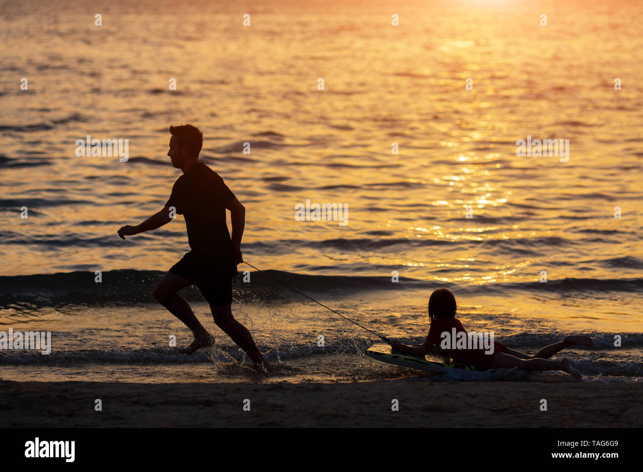 silhouette Father and kid playing on the beach the sunset time. Father and kid having fun outdoors Stock Photo