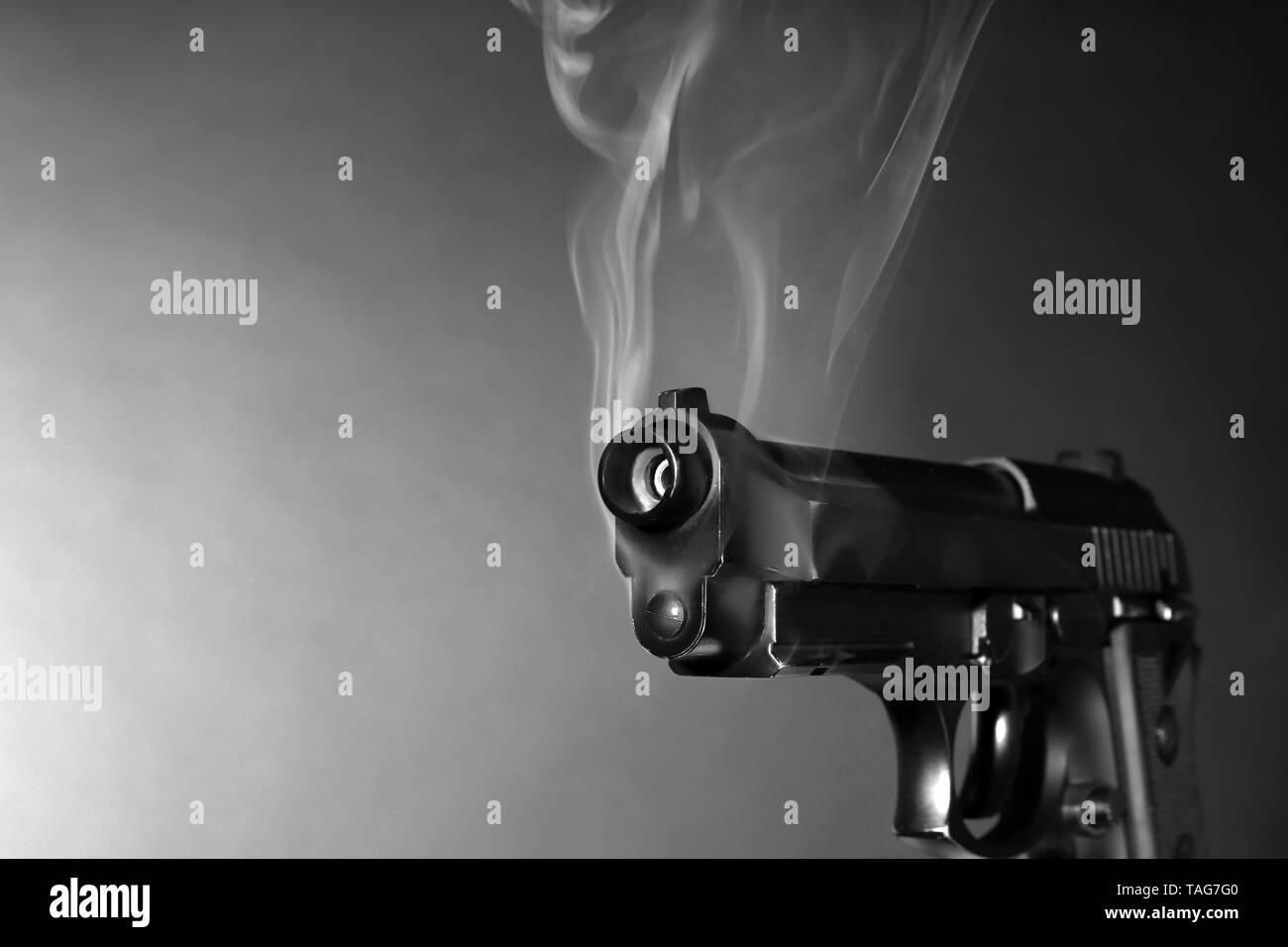 Smoking gun on dark background - Stock Image