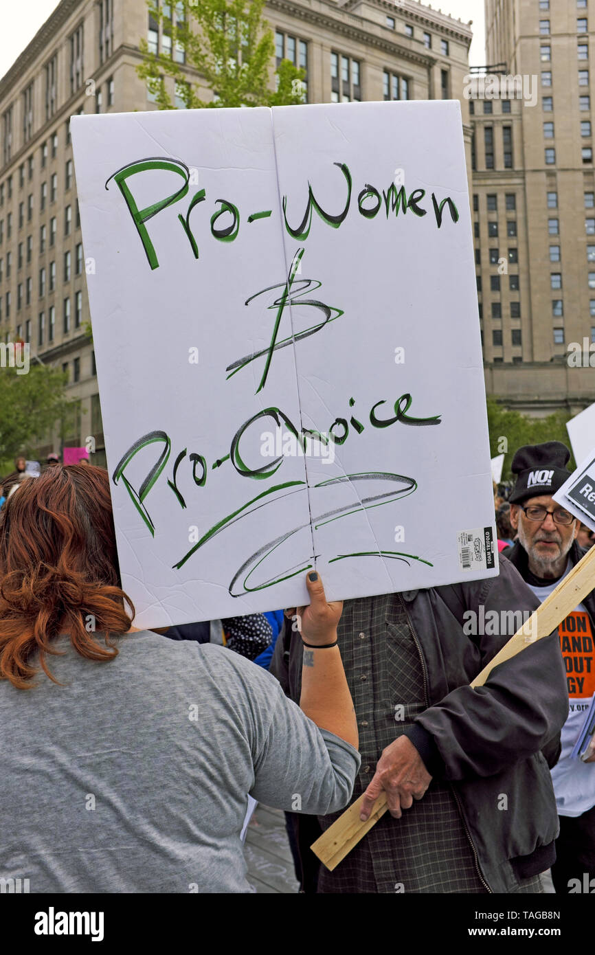 A woman holds a sign stating 'Pro-Women & Pro-Choice' at a rally on Public Square in Cleveland, Ohio, USA protesting changes to Ohio abortion laws. - Stock Image