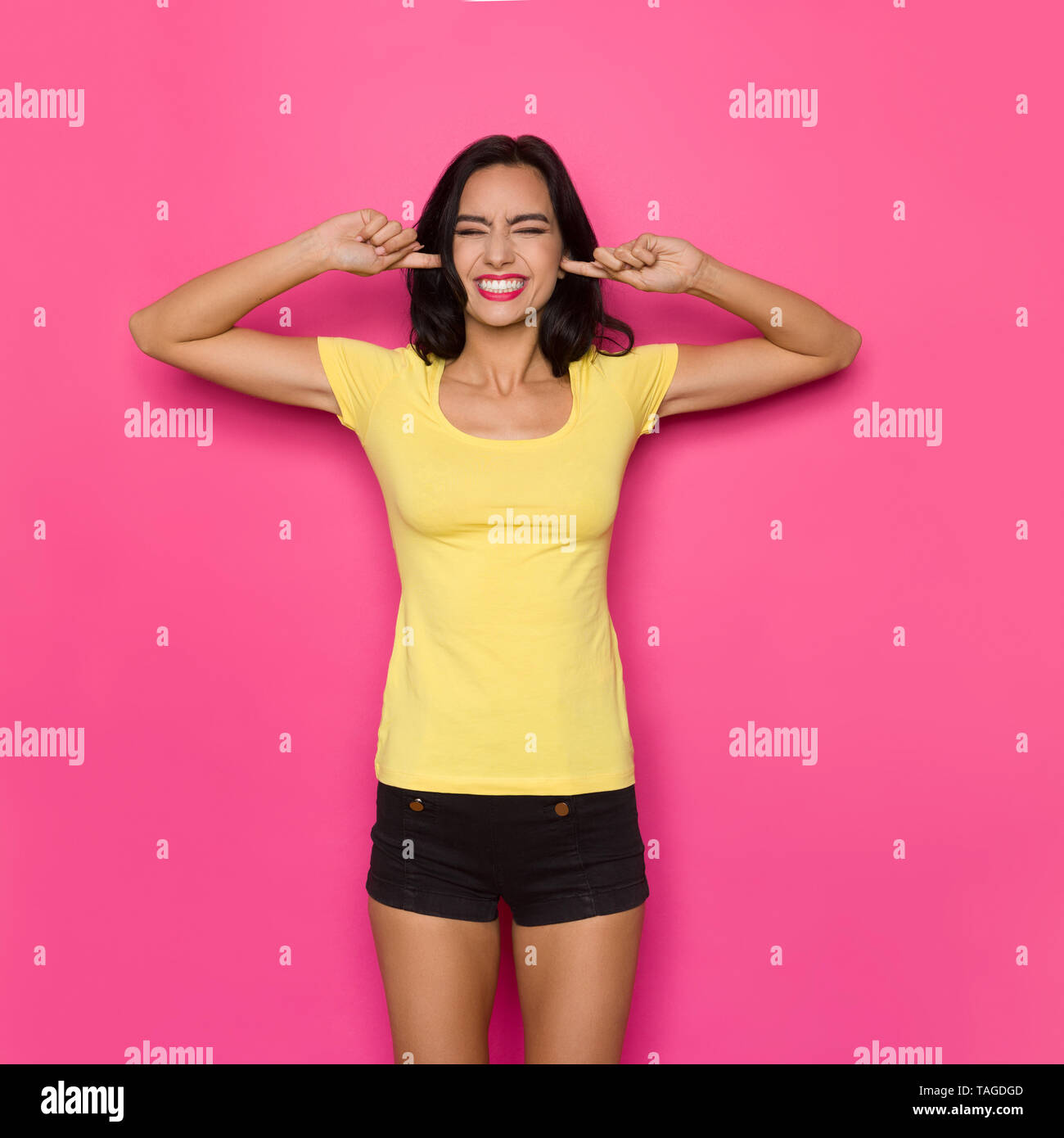 Beautiful young woman in yellow shirt and black shorts is holding index fingers in ears, closing eyes and grimacing. Three quarter length studio shot  - Stock Image